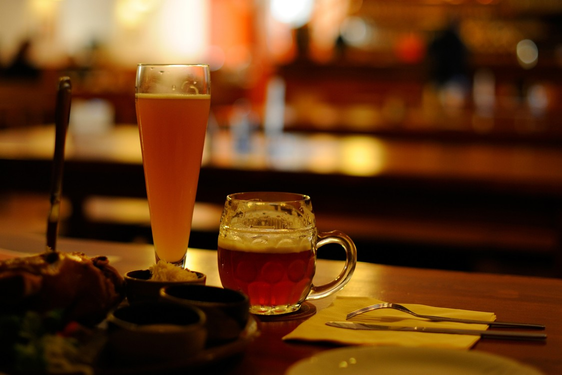 A glass of  beer next to a mug of beer on a bar top
