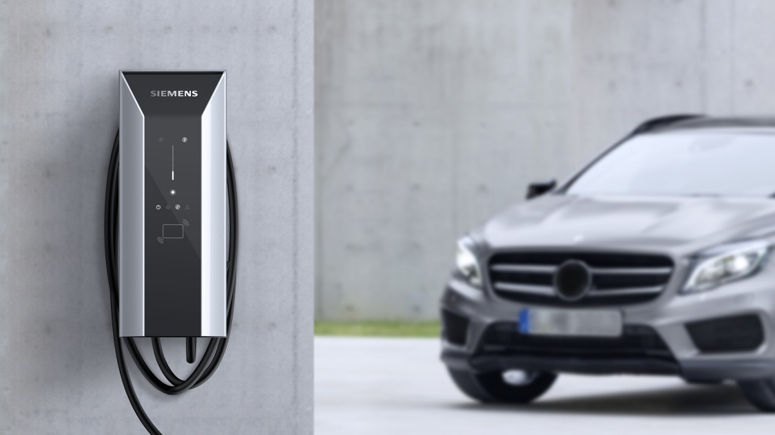 Siemens Versicharge wallbox with a car in the background