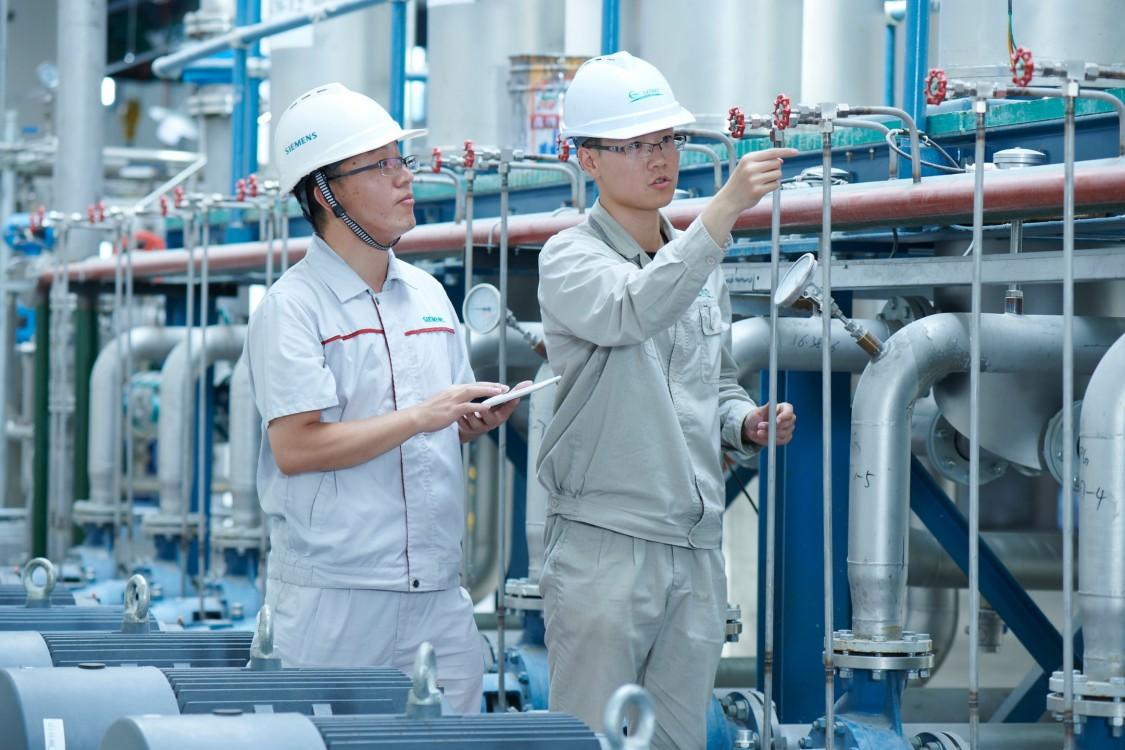 Praxisschulung eines Cathay-Mitarbeiters in der biotechnologischen Fertigung durch einen Siemens Mitarbeiter in der Anlage.