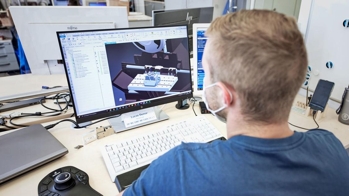 Das Bild zeigt einen Mitarbeiter der Siemens Elektromotorenfertigung in Bad Neustadt an seinem Schreibtisch sitzend. Auf dem Schreibtisch stehen zwei Monitore. Auf dem linken sieht man den digitalen Zwilling eines Motors, der zweite Monitor ist vom Kopf des Mitarbeiters verdeckt.