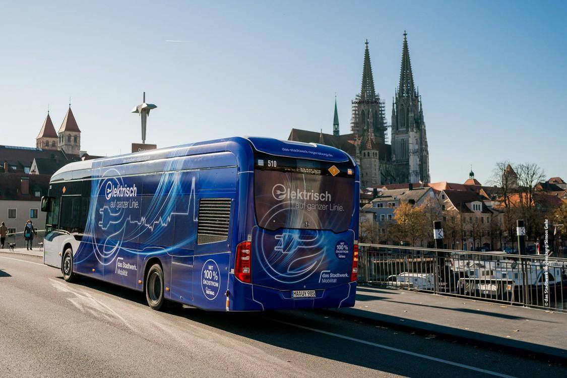 Un autobuz albastru de transport public cu motor electric circulă printr-o stradă din Regensburg, Germania