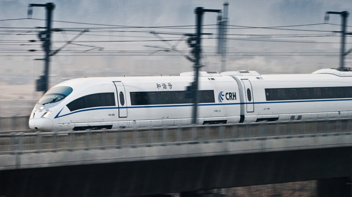 Image of the Velaro CN from Siemens Moblity in a slight diagonal view and motion blur driving on a rail track.