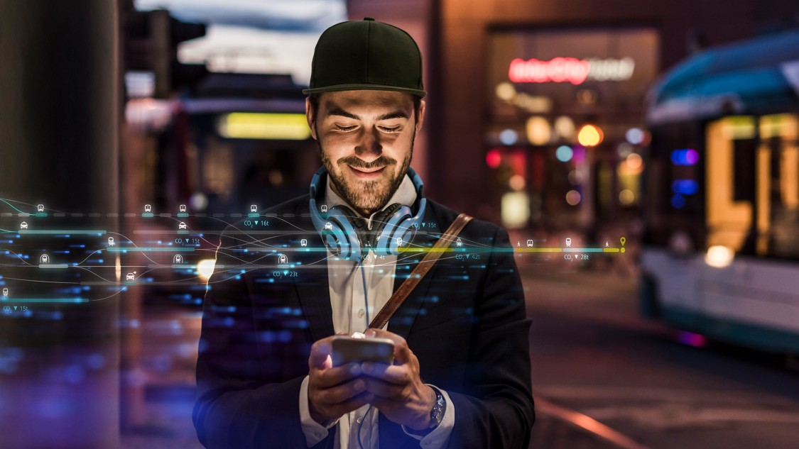 A young man wearing a baseball cap stands in an urban environment by night and looks at his smartphone with a smile. In the foreground a light effect as a symbol of digitalization.