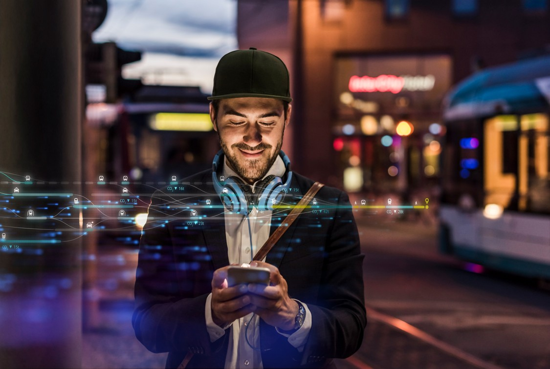 Ein Mann schaut auf sein Mobiltelefon; digitale Symbole, welche für die Digitalisierung der Mobilität stehen, überlagern das Bild