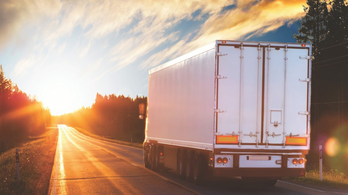 Lorry on road at sunset