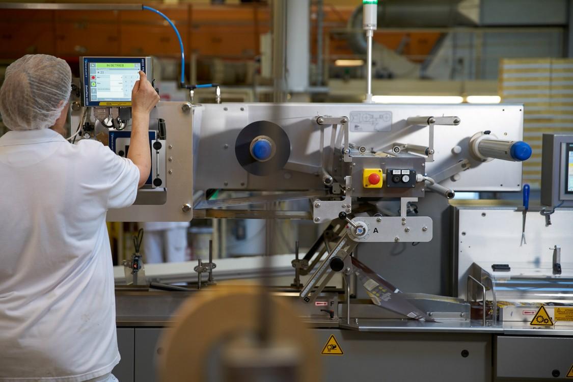 funcionária de fábrica de alimentos usando toca de cabelo e roupas brancas clica em tela de aparelho do sistema de produção automatizada