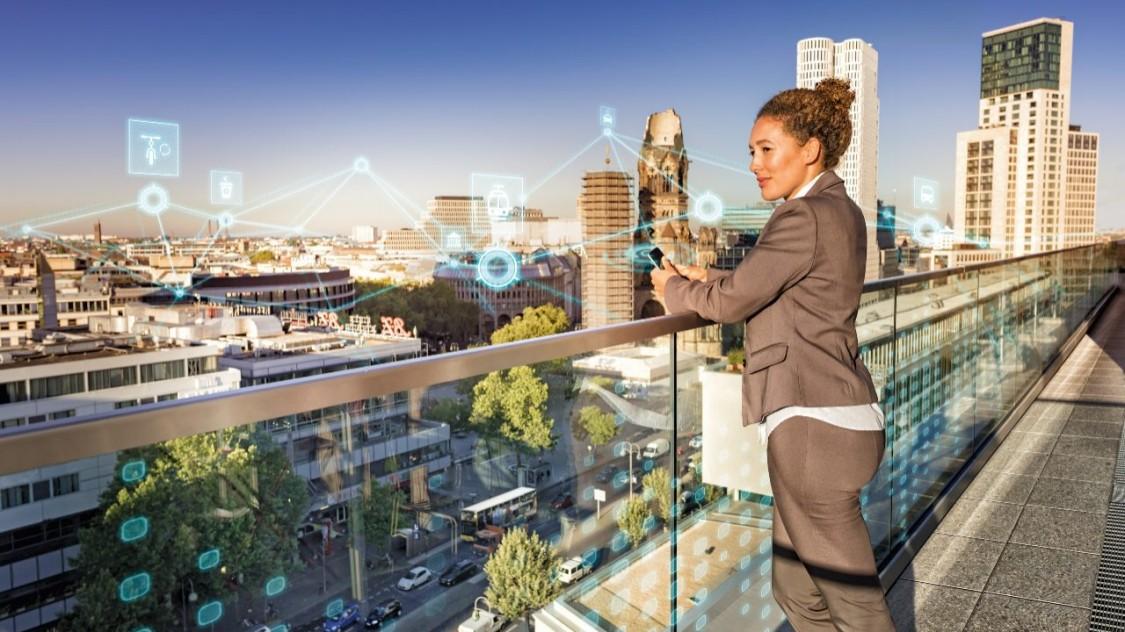 Frau mit goldbraunen Locken im Business-Outfit hat ein Handy in der Hand und schaut aus einer Terrasse über den Strassenverkehr einer Stadt