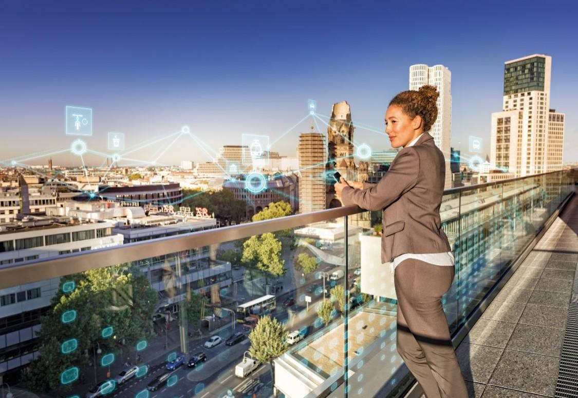 Businessfrau ist auf Aussichtspunkt schaut über eine Stadt mit intelligenter Mobilität