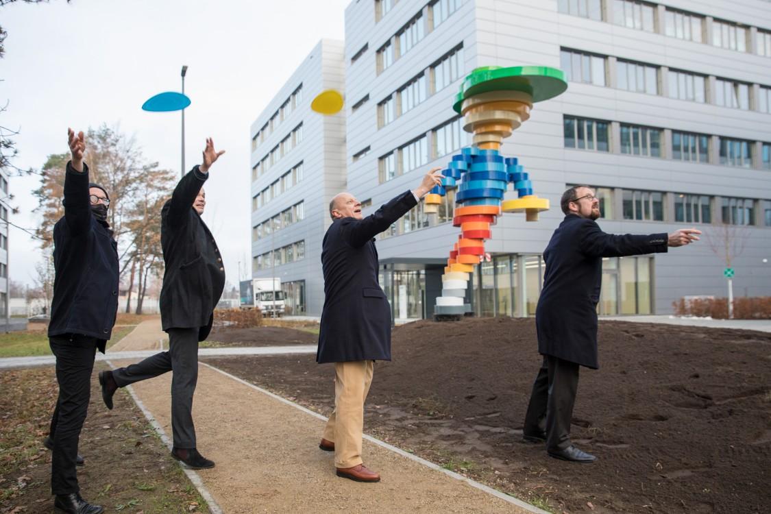 4 Männer werfen Frisbees vor dem Kunstwerk