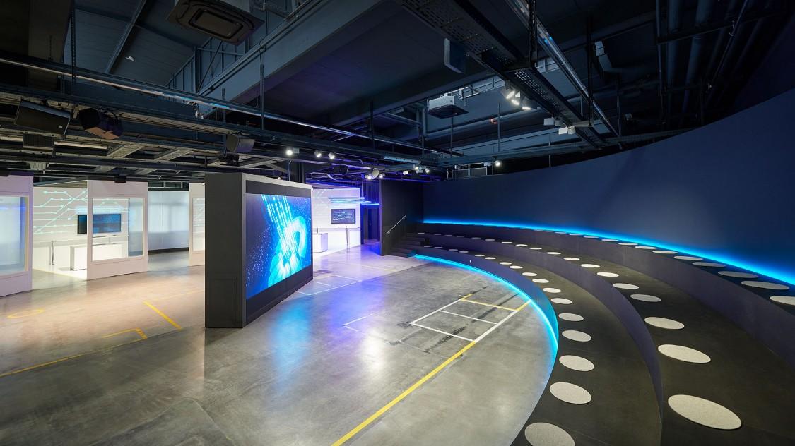Großflächige Tribüne vor dem großen Bildschirm in der Arena der Digitalisierung.