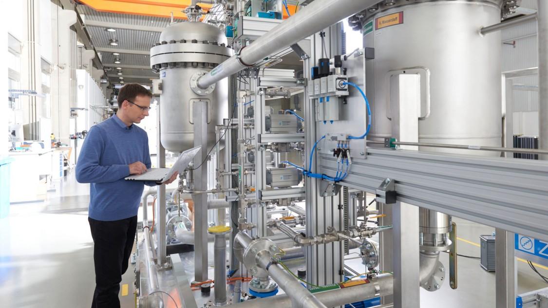Mitarbeiter vor Apparateaufbau dokumentiert ein Elektrolyseverfahren.
