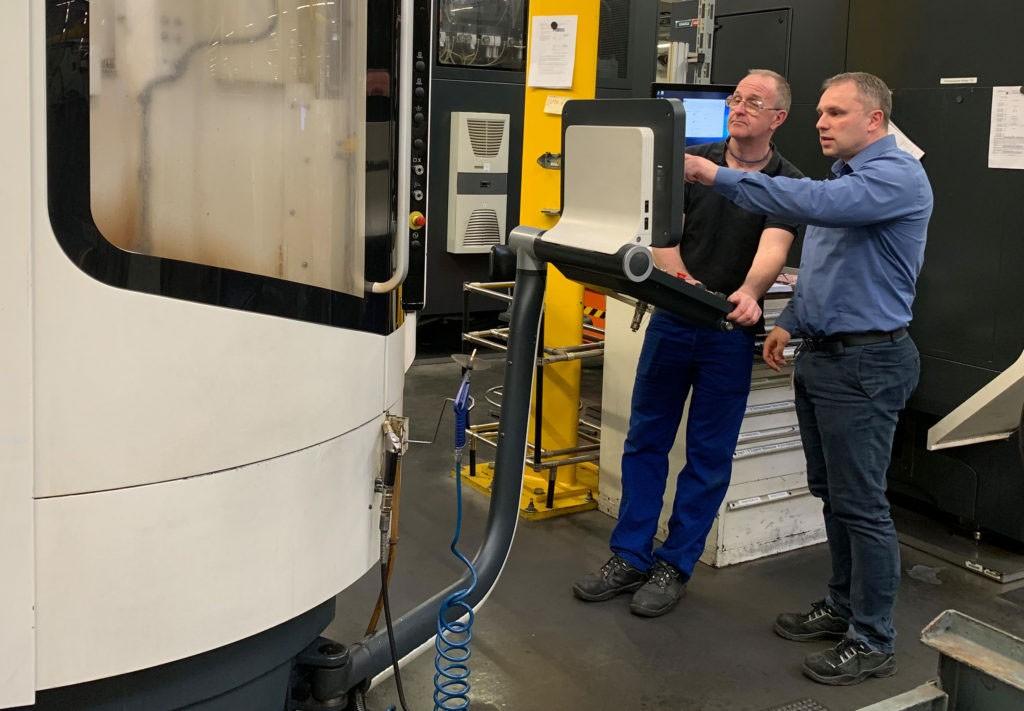 Das Bild zeigt zwei Mitarbeiter der Siemens Elektromotorenfertigung in Bad Neusadt. Gemeinsam stehen sie an der adaptiven Prozessüberwachung und -steuerung ACM (Adaptive Control & Monitoring), mit der sie den Kernprozess der Zerspanung optimieren.