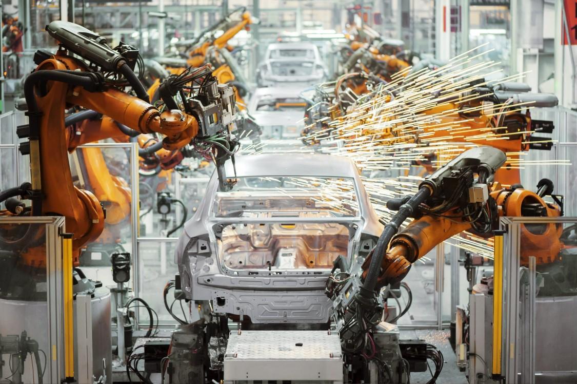 Wir blicken frontal auf die Fertigungsstraße eines Automobilherstellers: orangefarbene Roboterarme führen Schweißarbeiten an Karosserien aus. Funken sprühen.