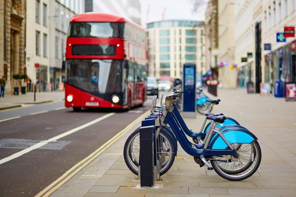 Bicicleta azul estacionada em calçada e ao fundo um ônibus vermelho