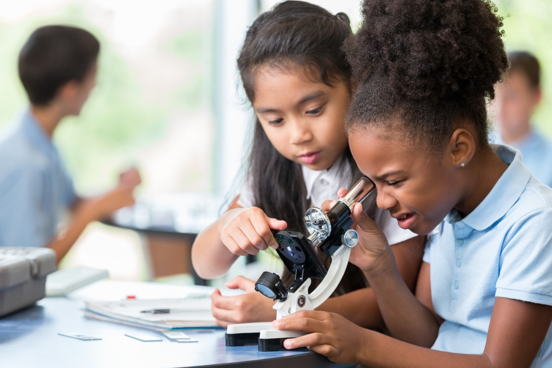 Focused African American and Asian schoolgirls help one another with their assignment in science class at a STEM elementary school.