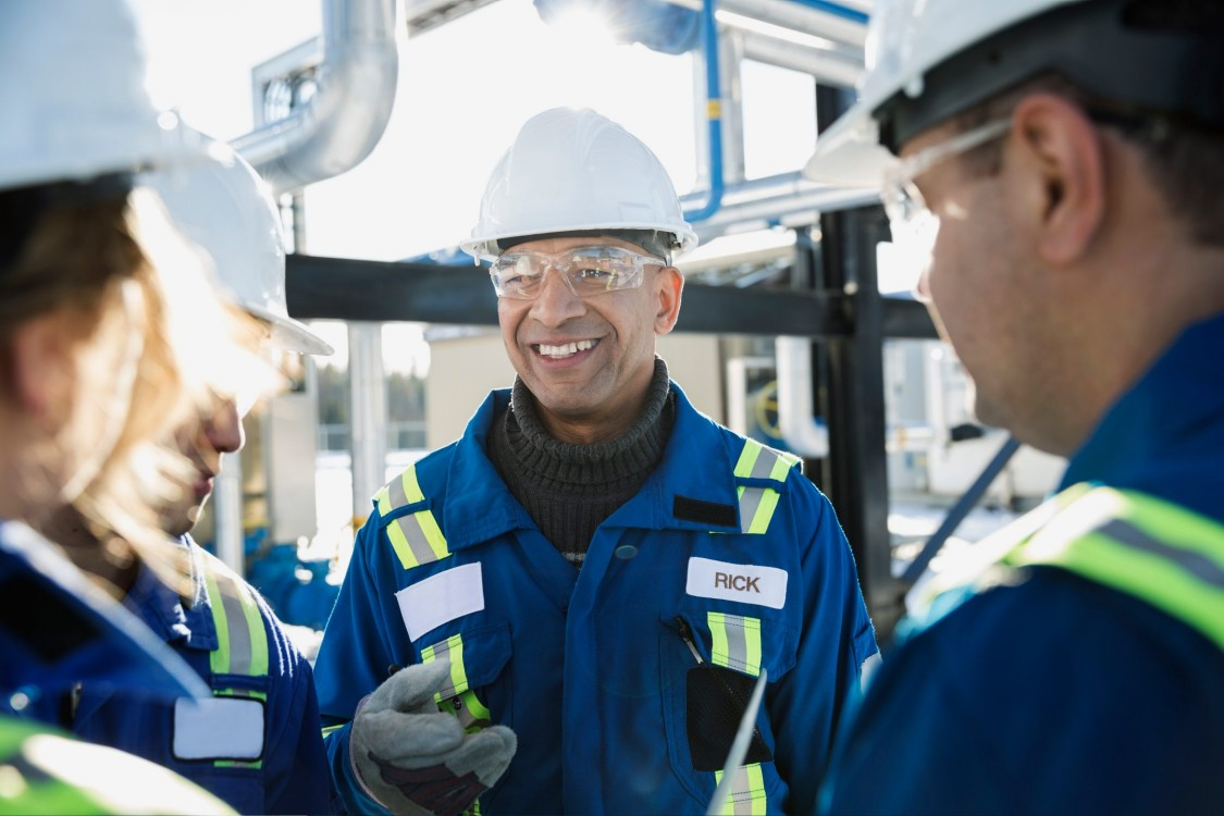 Smiling workers talking at gas plant