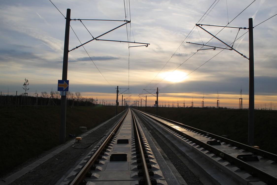 Weite Sicht auf die Gleise mit einem warmen Sonnenuntergang am Horizont