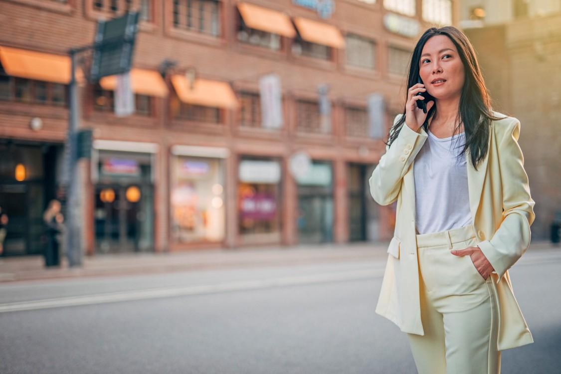 Eine Frau Mitte 30 in einem weißen Anzug steht neben einer Straße mit urbanem Charakter. Sie telefoniert mit ihrem Smartphone.