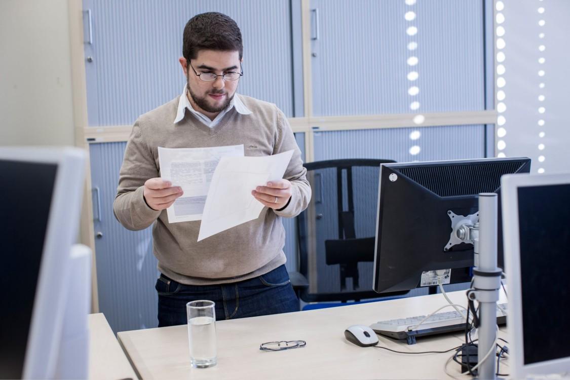 Stefano steht an seinem Schreibtisch und  liest Unterlagen