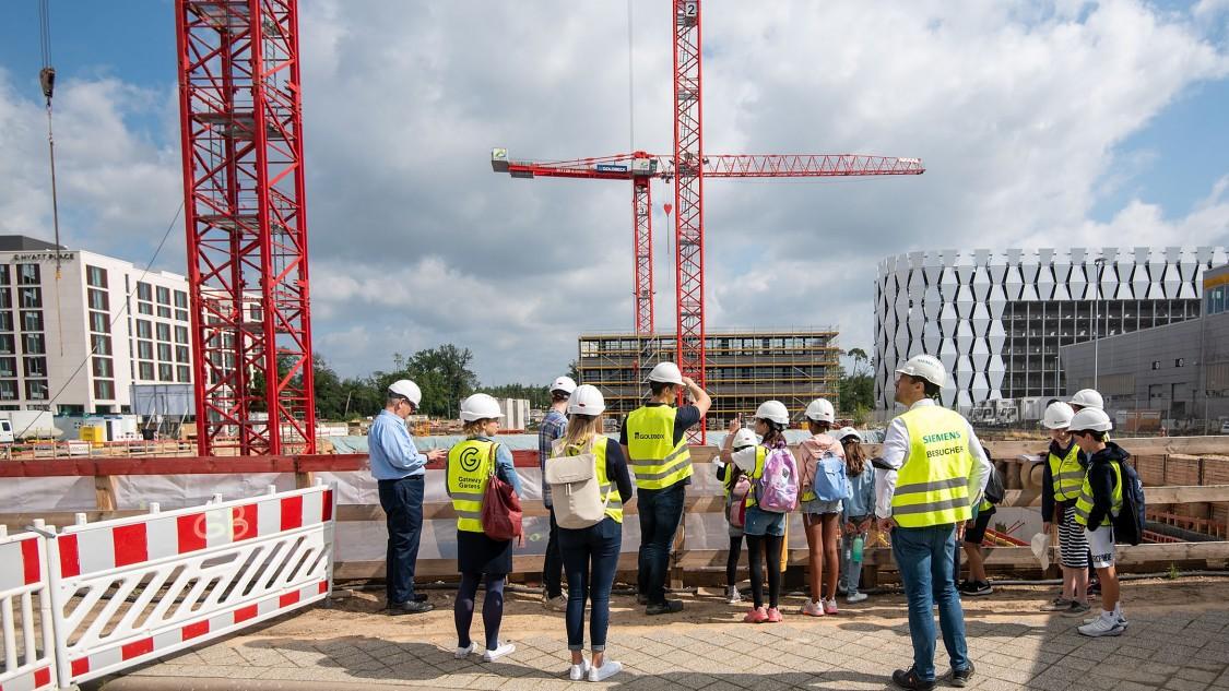 Zwei 5. Klassen der Metropolitan School Frankfurt und ihren Begleitpersonen auf der The Move Baustelle in Gateway Gardens
