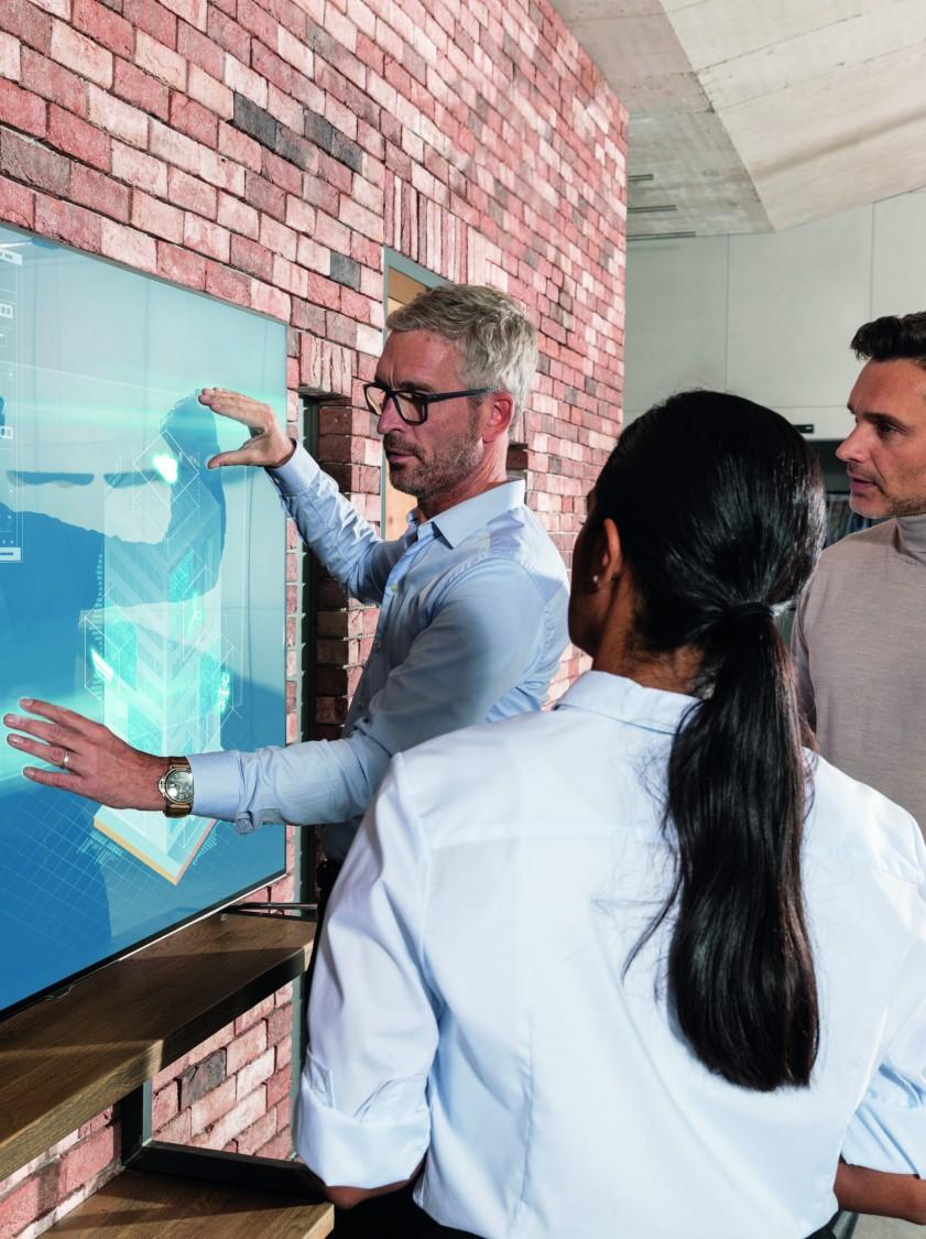 Personen begutachten einen Plan an einer digitalen Wand