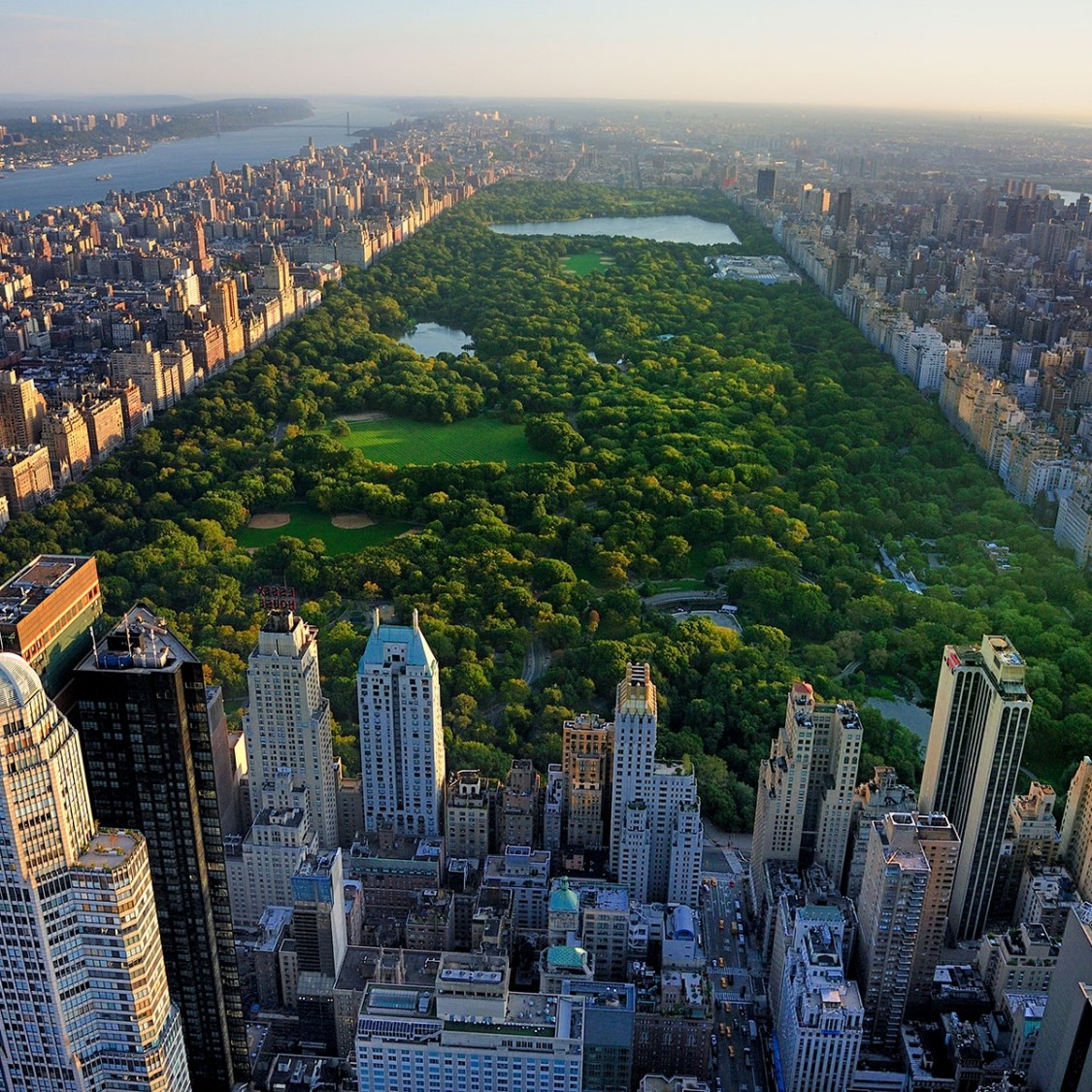 Moody aerial view of Central Park in New York as the green heart of the city surrounded by tall buildings