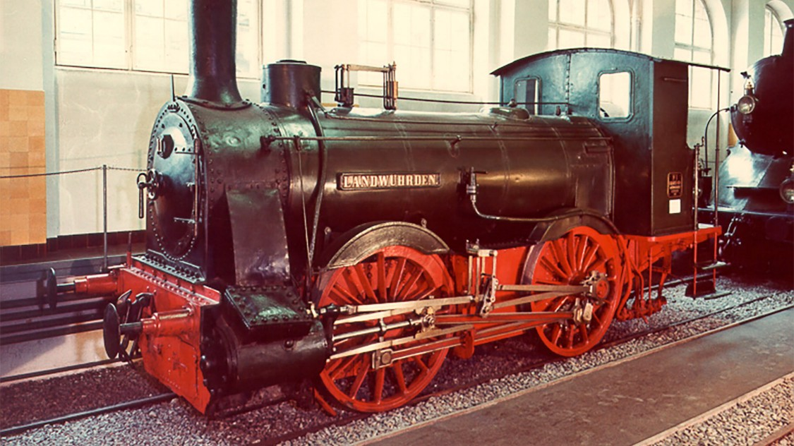 """A segunda fábrica de locomotivas em Munique, fundada por G. Krauss, começou a construir locomotivas em 1867. Sua primeira locomotiva tinha o nome de """"Die Landwührden."""" Mil locomotivas foram entregues em 1882, e a marca de 8.000 locomotivas é alcançada em 1923."""