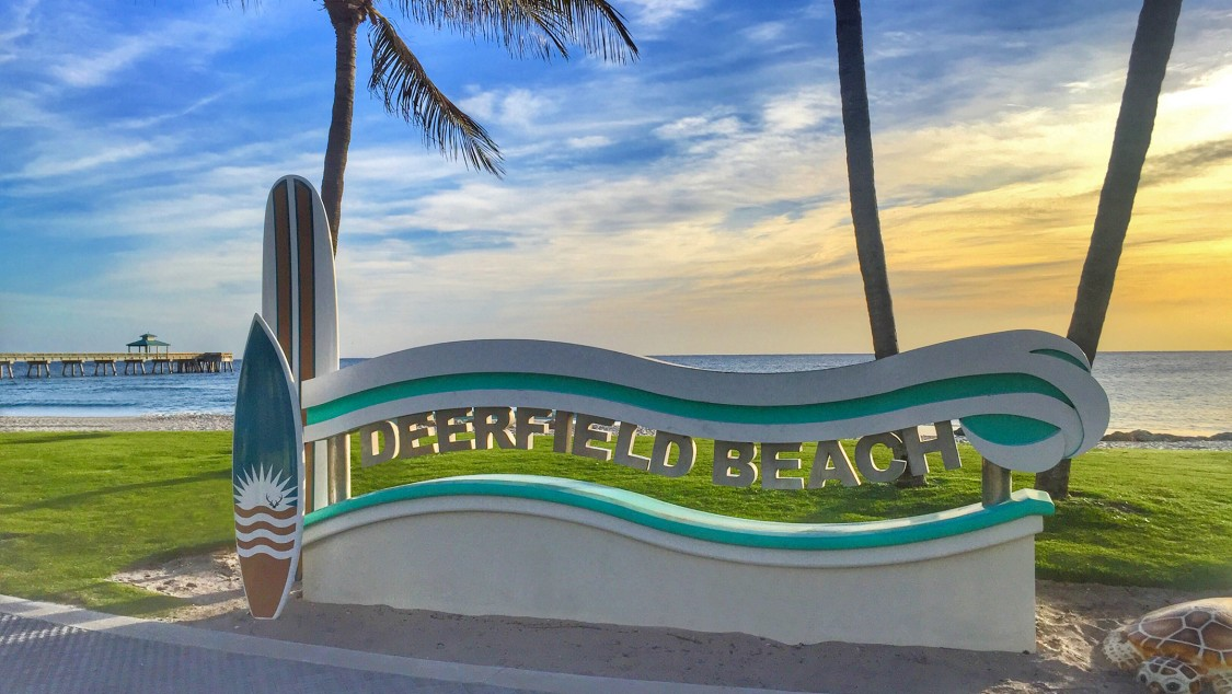 Deerfield Beach sign lined with Palm trees