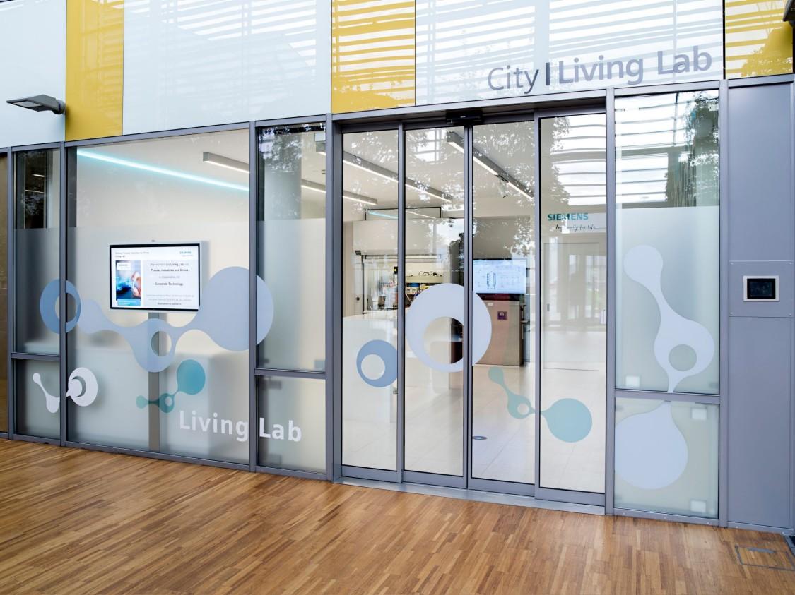 Gläserne Eingangstür zu Räumen der Forschungseinrichtung Living Lab in Wien.