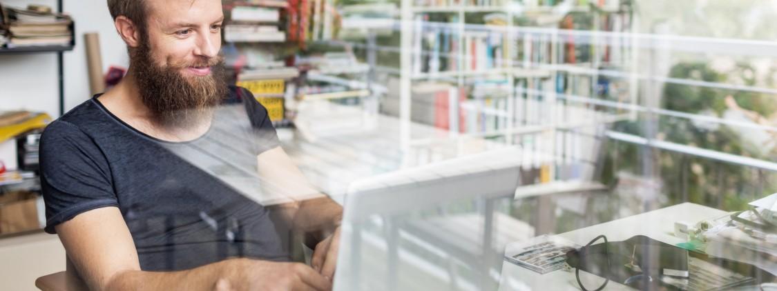homem barbudo de camisa cinza trabalhando em frente de computador sorrindo demonstrando a seguranca em seu trabalho de home office