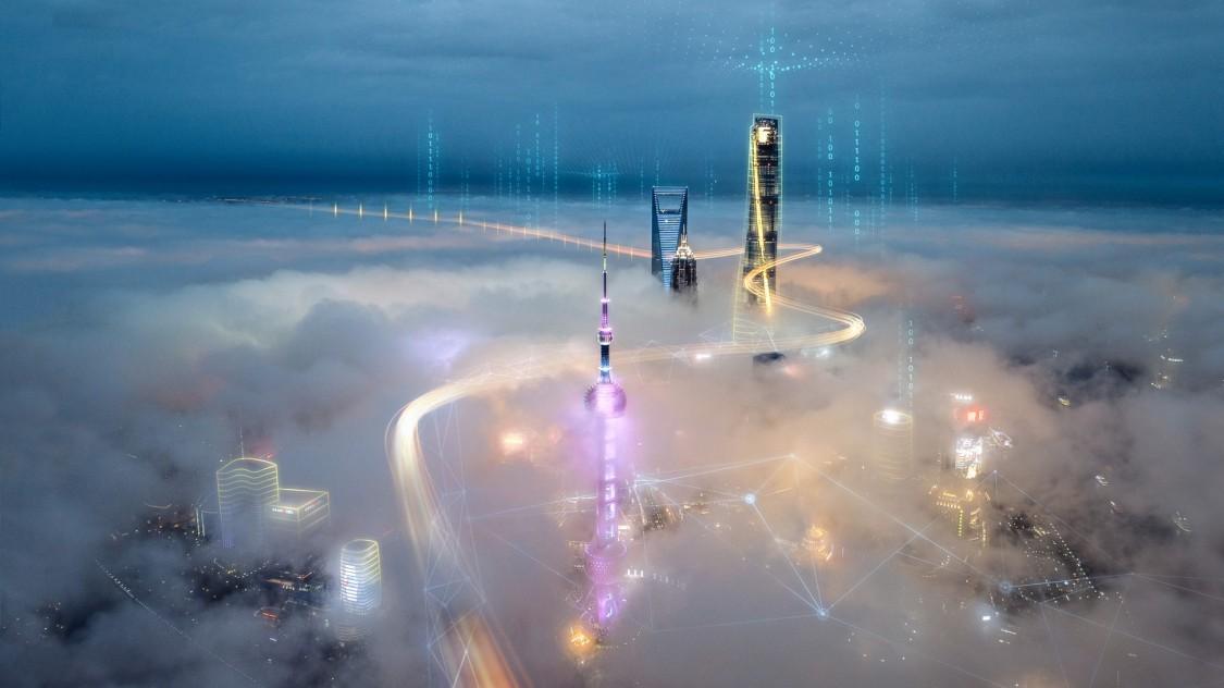 imagem aérea de uma grande cidade coberta por uma neblina acima dela três topos de prédios estão conectados através de filtro de tecnologia representando a ligação dos gêmeos digitais elétricos