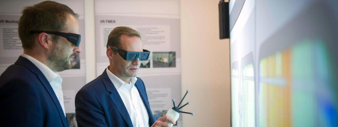 O Dr. Hagen Gehringer, diretor da Bausch + Ströbel Maschinenfabrik Ilshofen GmbH e Klaus Helmrich, membro do conselho de administração da Siemens AG, usando oculos de realidade aumentando em frente a um monitor