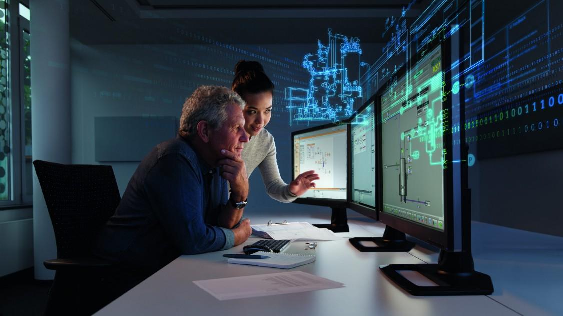 Zwei Ingenieure betrachten auf mehreren Monitoren Anlagendaten, die als Hologramm im Hintergrund sichtbar sind