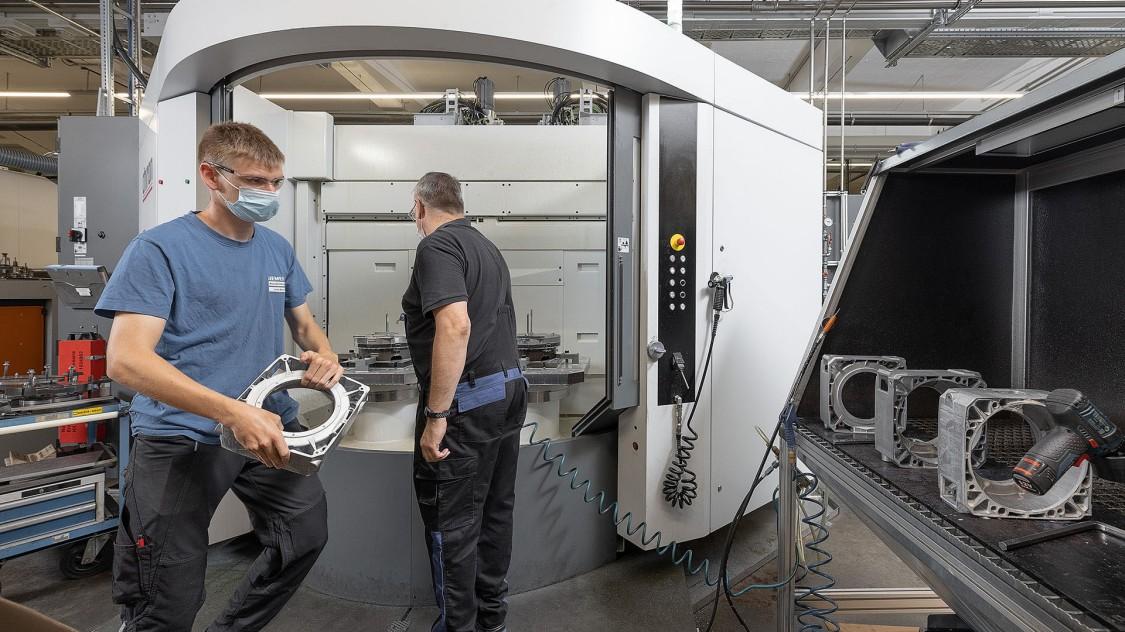 Im Bild zu sehen sind zwei Mitarbeiter im Fertigungsbereich der Siemens Elektromotorenfertigung in Bad Neustadt. Rechts von ihnen sind diverse Bauteile von Elektromotoren zu sehen.