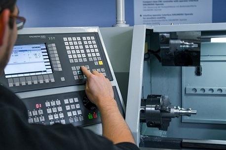 homem de óculos clica em botão em painel que utiliza o software sinumerik 808d no pc v4.4