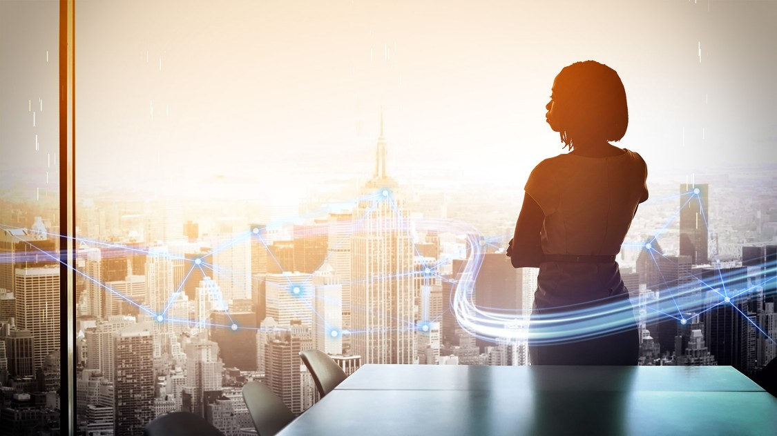 woman standing on office on high rise looking out window at skyline