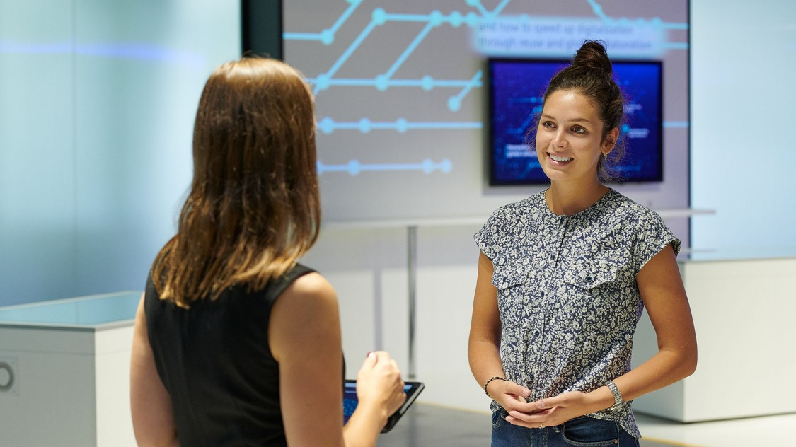 Two women chatting about digital transformation in the center of the Arena of Digitalization – one of the theme rooms is partly visible in the background.