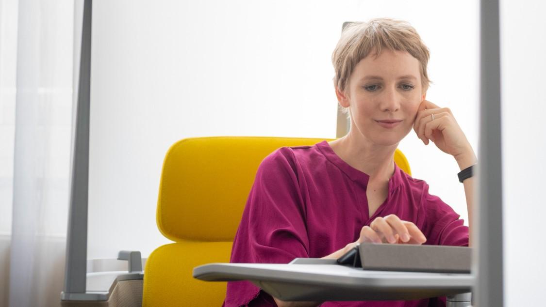 Frau mit lila shirt stizt auf einem gelben Sessel und bedient ein Tablet