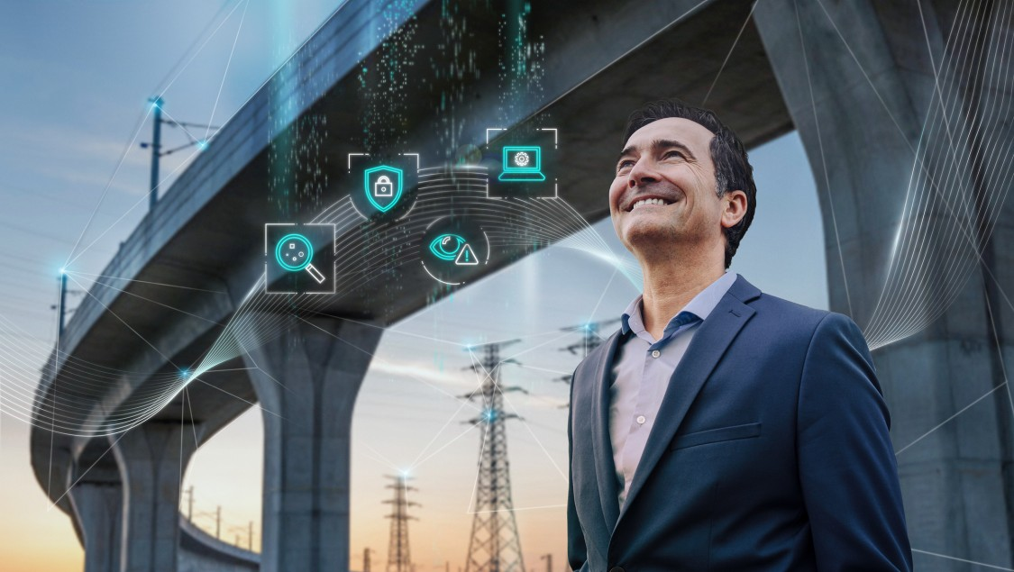 A man stands in front of an elevated highway with electrical power lines in the background. The digital layer has four icons representing the different stages of implementing a robust cybersecurity regime (identify, protect, detect, manage) for critical infrastructure networks.