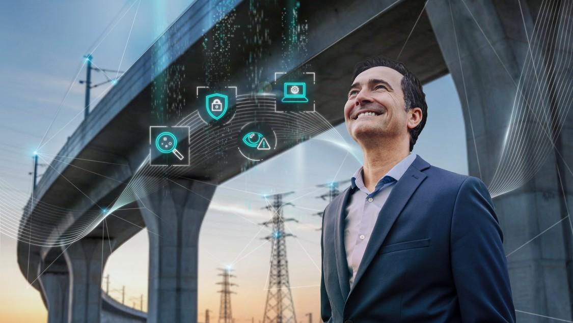 Ein Mann steht vor einer Autobahnbrücke mit elektrischen Stromleitungen im Hintergrund. Der digital Layer hat vier Icons, die die verschiedenen Phasen der Implementierung eines robusten Cybersecurity-Systems für kritische Infrastrukturnetzwerke repräsentieren (identifizieren, schützen, erkennen, managen).