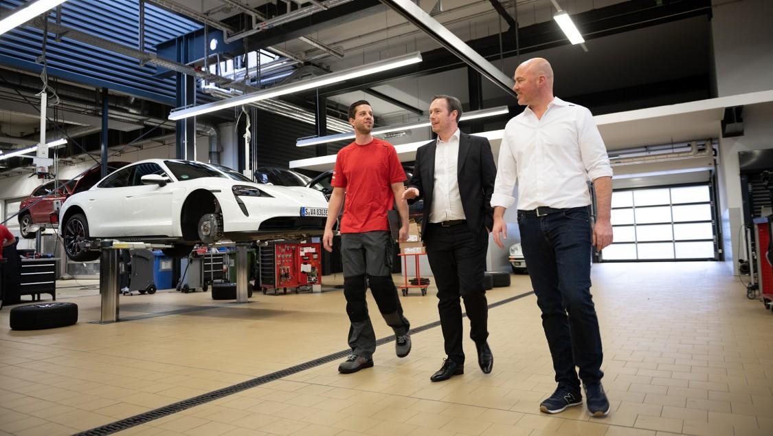 Robin Banse (solda) ve Marc Robl (sağda), şirketin Stuttgart-Zuffenhausen lokasyonundaki Porsche atölyesinde Siemens Sorumlusu Steffen Loose ile konuşuyor.