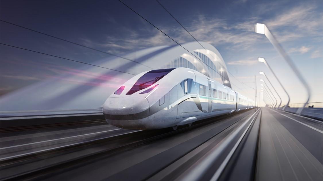 Bild des Velaro Novo von Siemens Mobility in Diagonalansicht von hinten bei der Fahrt über eine Brücke in leichter Bewegungsunschärfe.