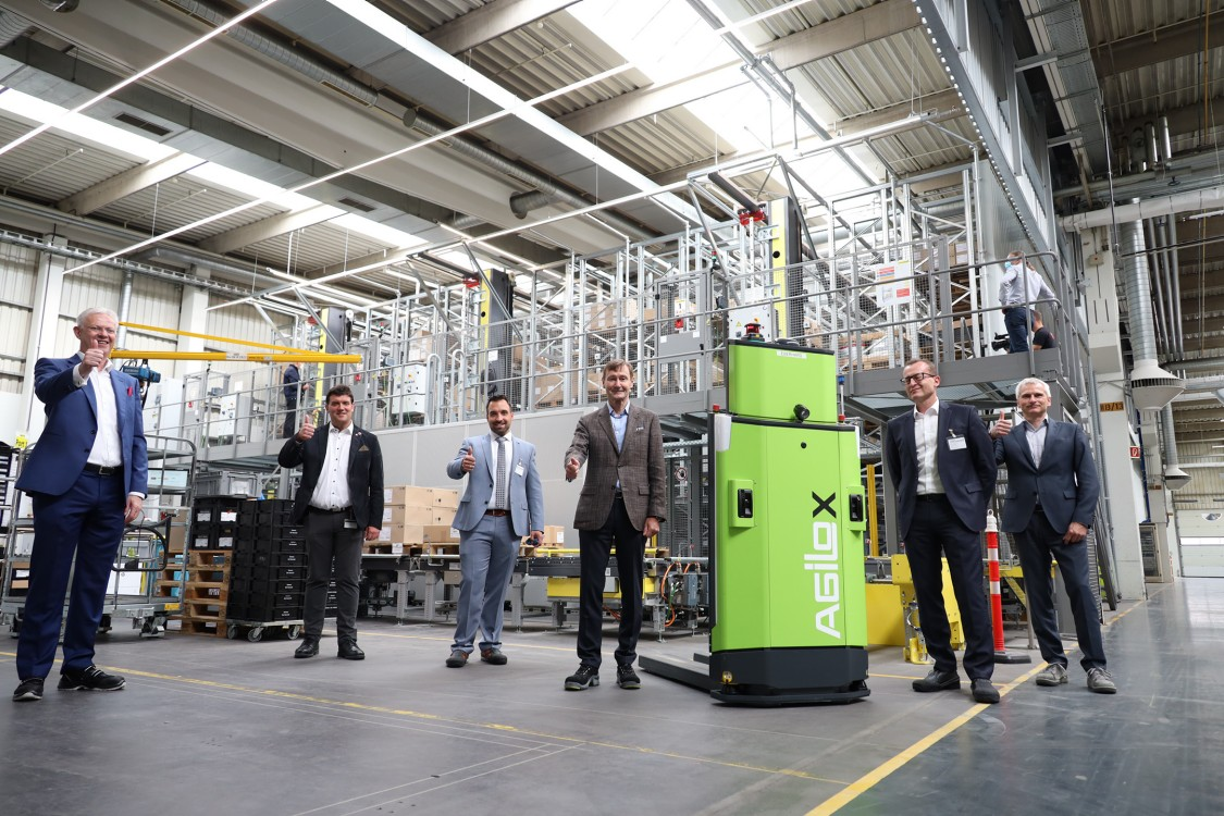 The image shows six managers in suits standing in the logistics center of Siemens Electric Motor Factory in Bad Neustadt, Germany, pointing their thumbs up. In their midst is a green Automated Guided Vehicle.