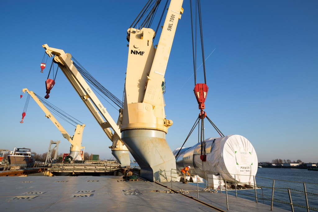 The ship's onboard crane loads the heavy cargo