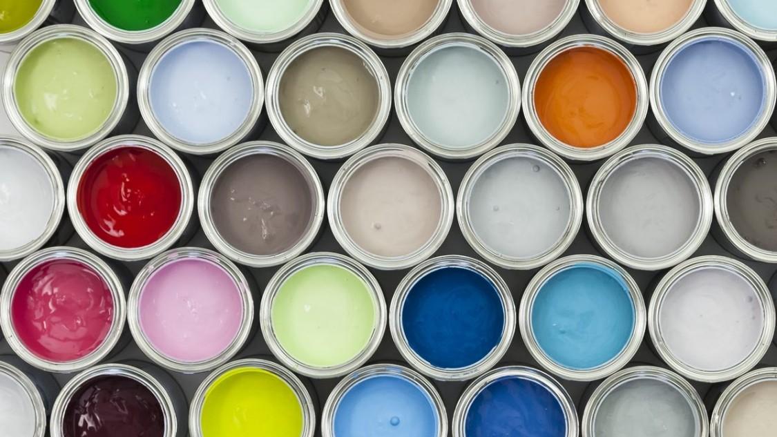 Вид сверху на открытые банки с краской различных цветов.
