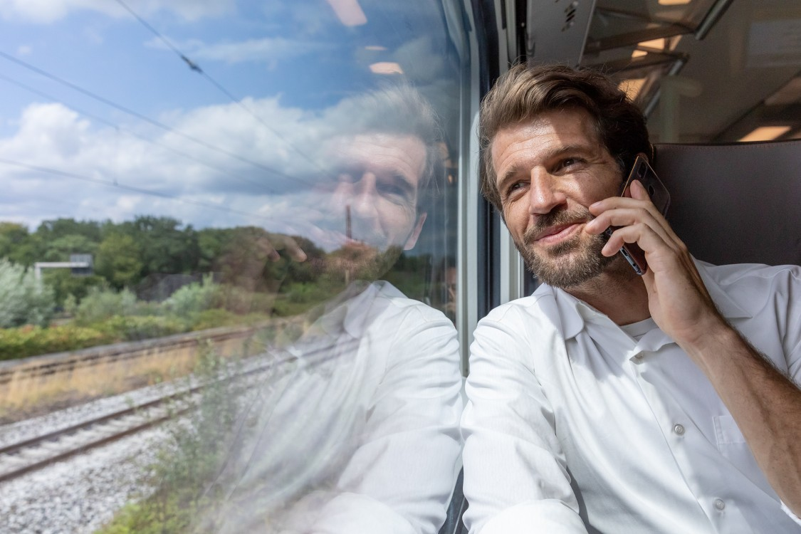 man sitting in train with smartphone