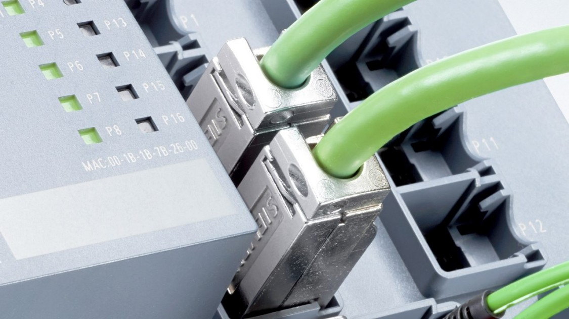 Close-up of green PROFINET cables plugged into hardware with green LEDs.