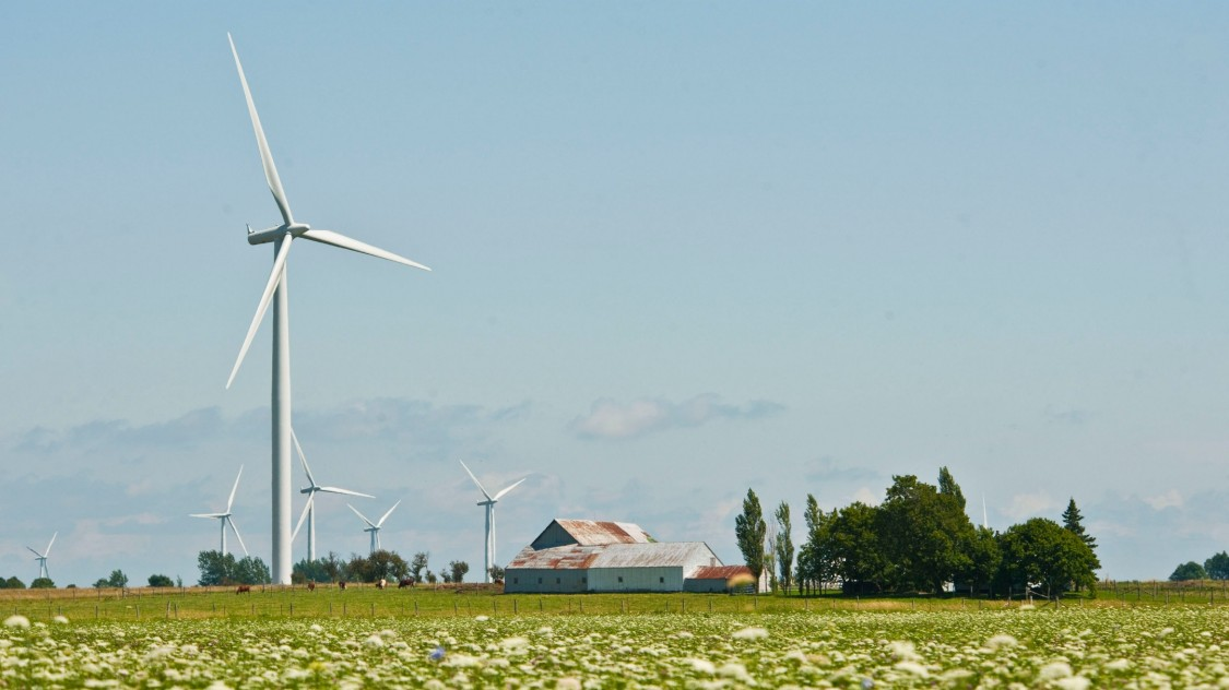 onshore wind turbines next to a farm