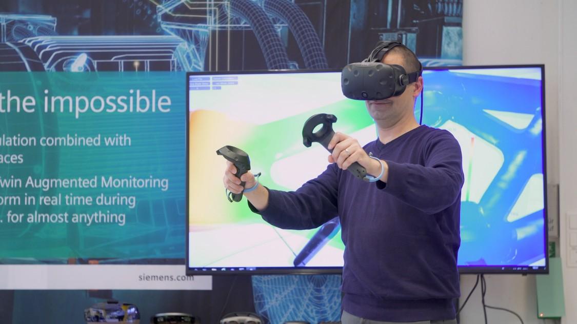 Dirk Hartmann von Siemens Corporate Technology testet mit interaktiven Simulationssoftware im virtuellen Raum, wie sich das Modell einer Radaufhängung verhält, wenn er es mit starken Kräften belastet.