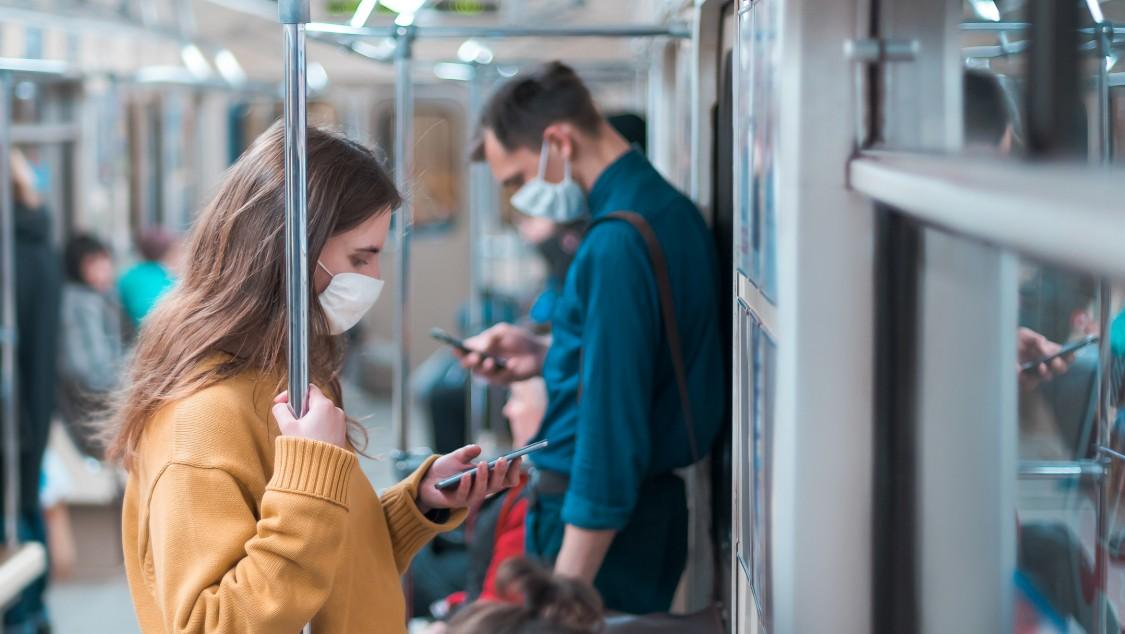 Zwei Passagiere mit Masken an Bord eines Zuges umgeben von Lösungen zur Risikominderung während einer Pandemie